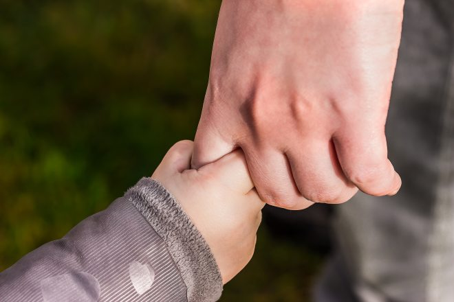 Child holding adults finger