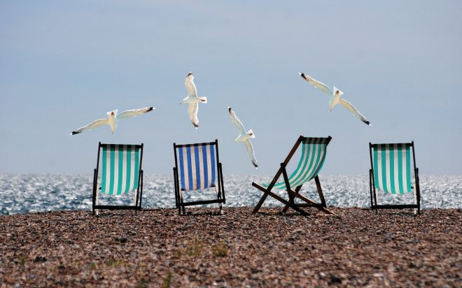 Four deckchairs on a beach