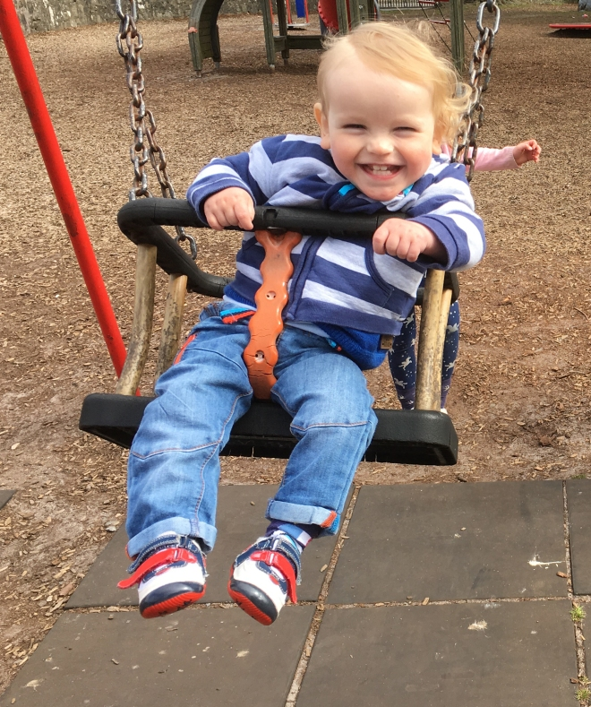 Quinns smiling on a swing