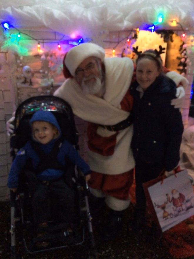 Quinns and Big Sister with Santa outside Santa's grotto