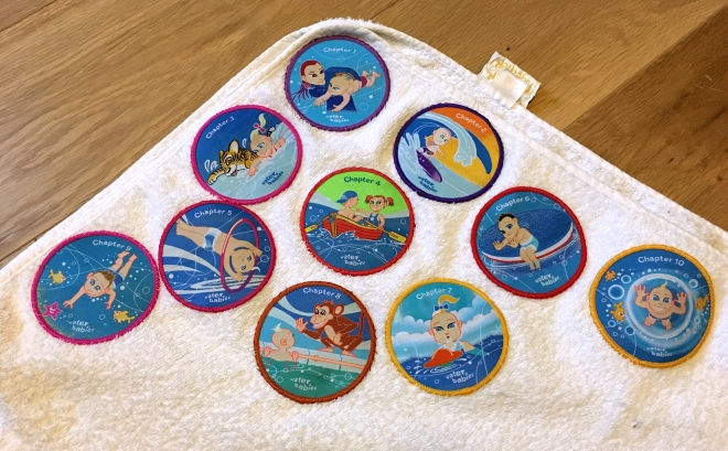 Photo of Quinns' swim badges sewn onto a towel