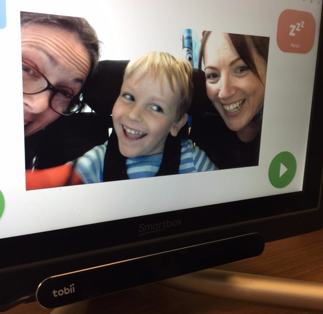 Photo of Quinns' eye gaze computer showing him taking a selfie with two others