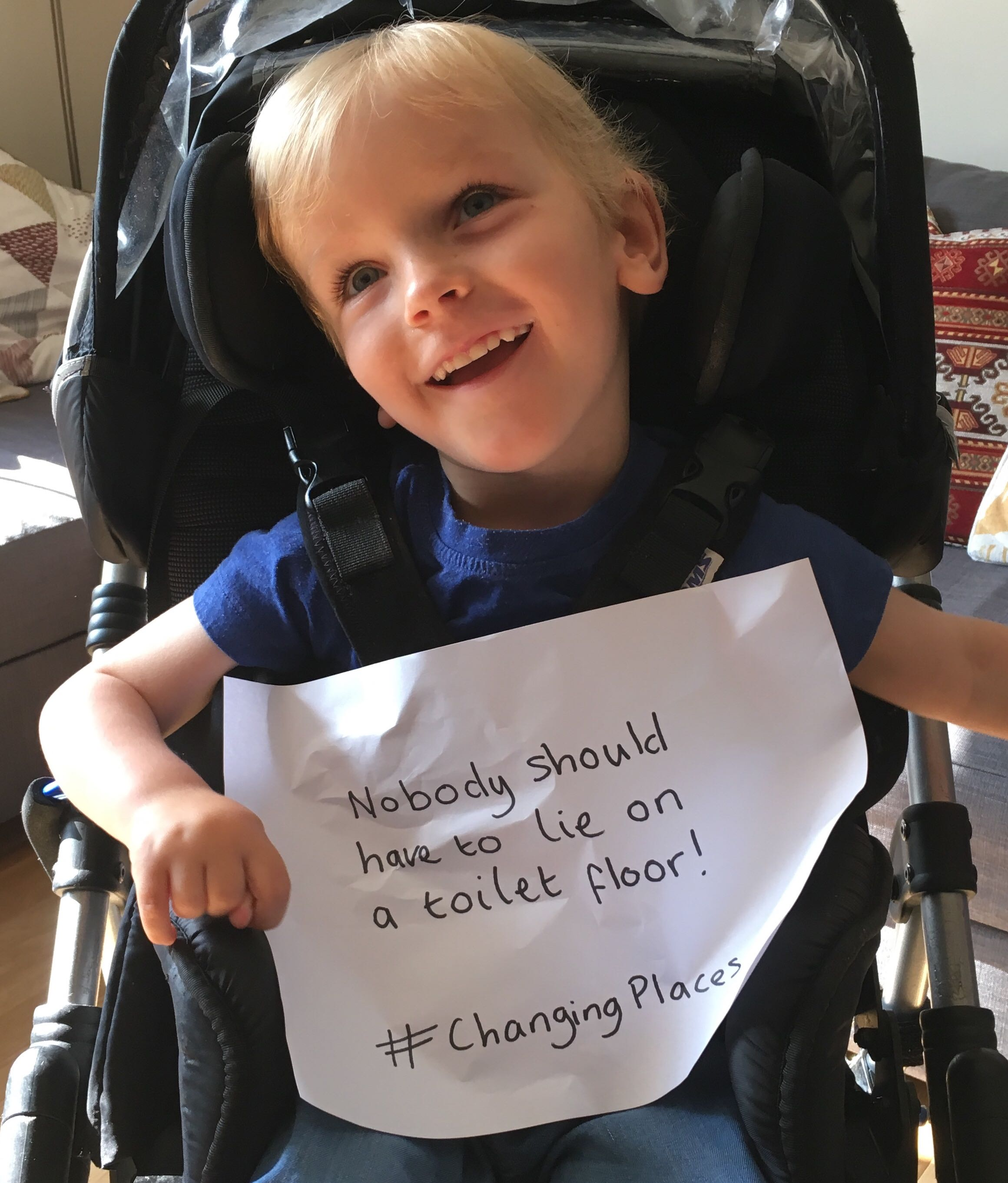 Photo of Quinns holding a handwritten sign that reads 'Nobody should have to lie on a toilet floor! #ChangingPlaces'