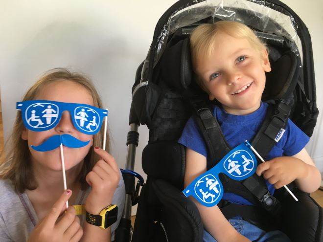 Photo of Quinns holding Changing Places paper glasses in his hand beside his Big Sister who is holding glasses and moustache up to her face.
