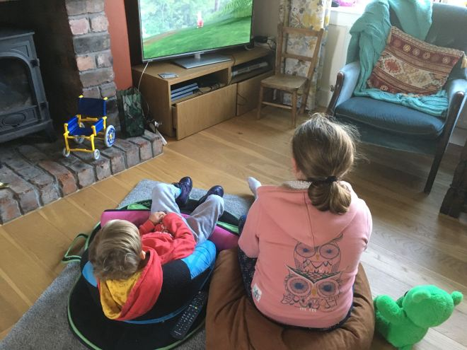 Photo of Quinns sitting in his Squiggles pack watching tv beside his Big Sister who is sitting on a bean bag. They are facing away from the camera and both are wearing hoodies.