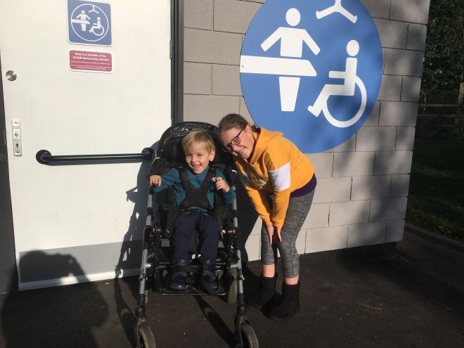 Photo of Quinns and his Big Sister outside a Changing Place toilet at a service station