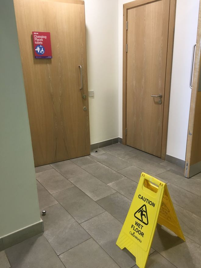 Photo of a sign saying 'Caution Wet Floor' outside a Changing Place Toilet