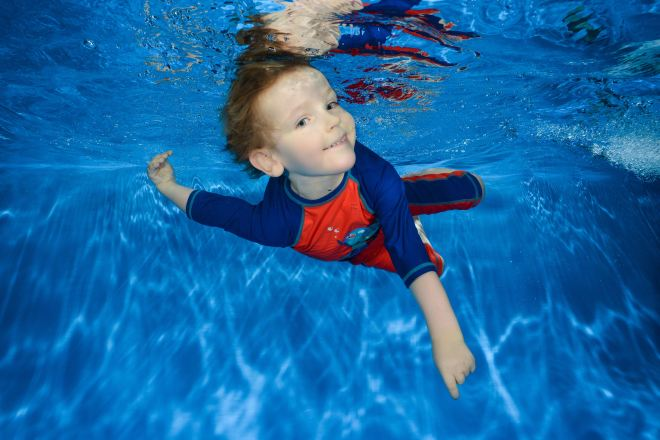 Photo of Quinns swimming underwater smiling at the camera