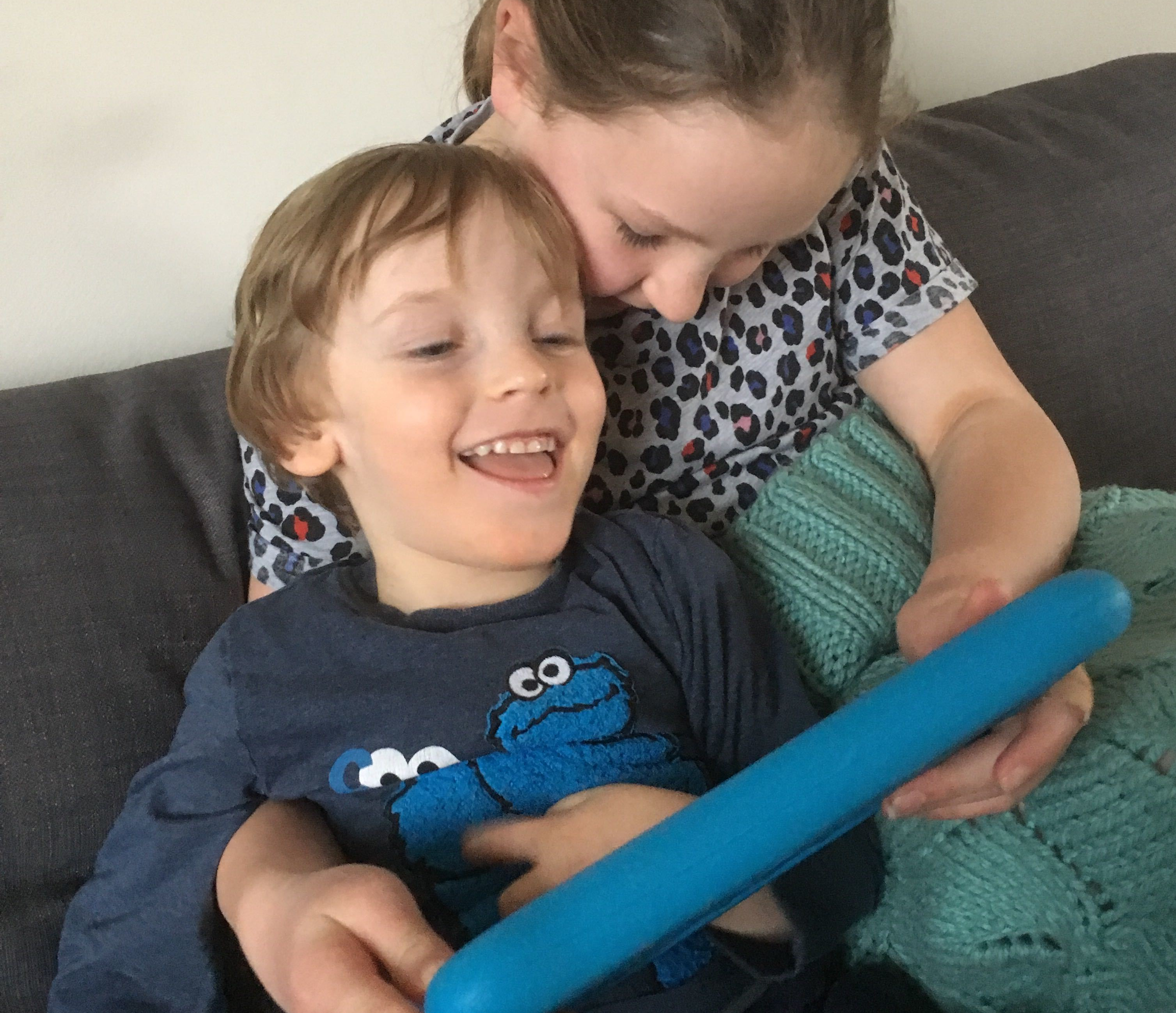 Photo of Quinns and his Big Sister together on the sofa playing on the tablet Big Sister is holding.