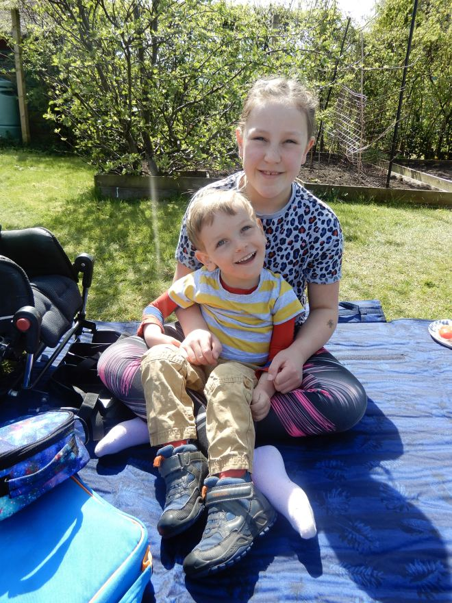 Photo of Quinns sitting on Big Sister's knee on a picnic mat with apple tree in the background.