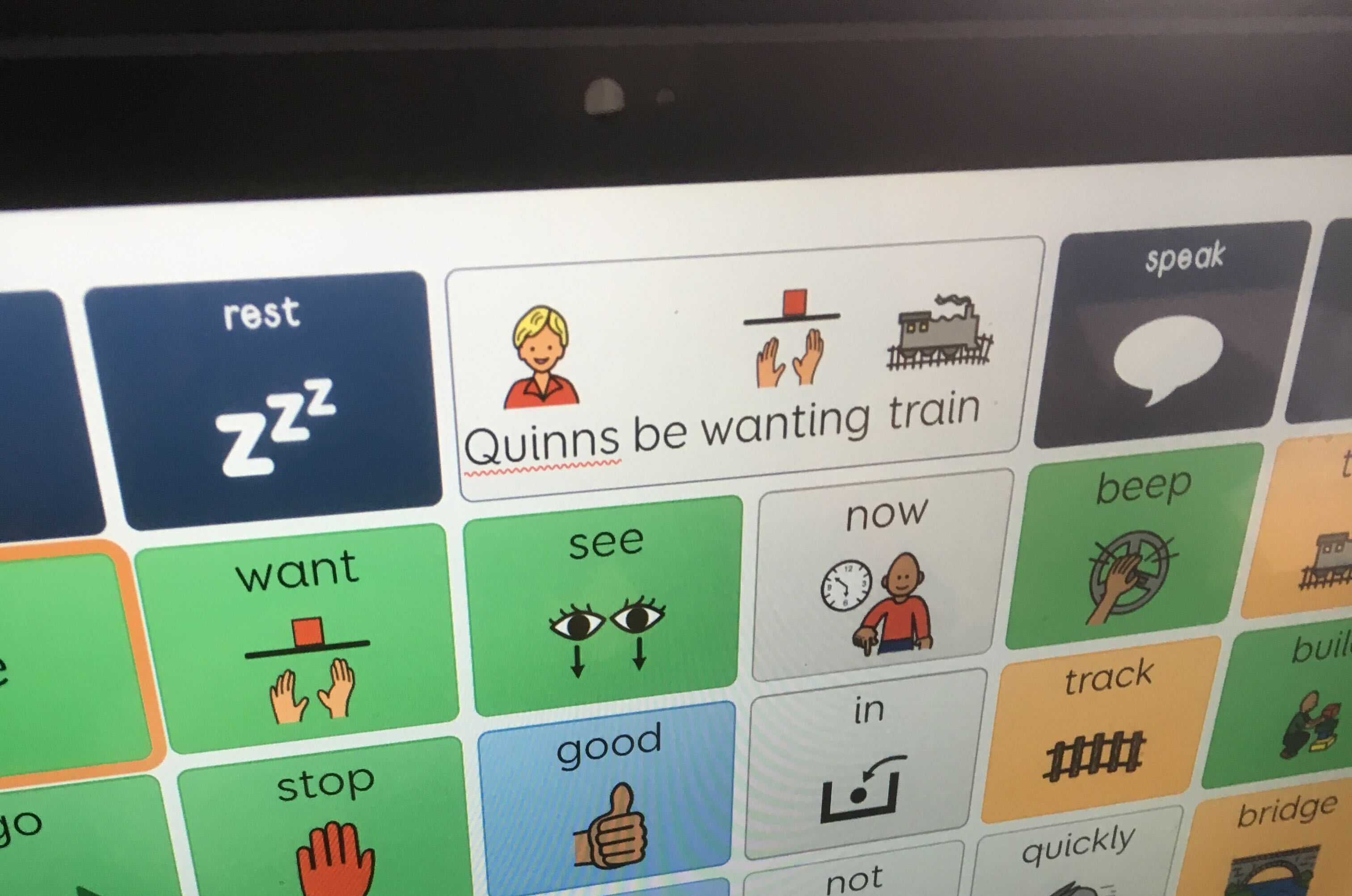 Photo of a eye gaze computer grid screen with the words 'Quinns be wanting train' selected