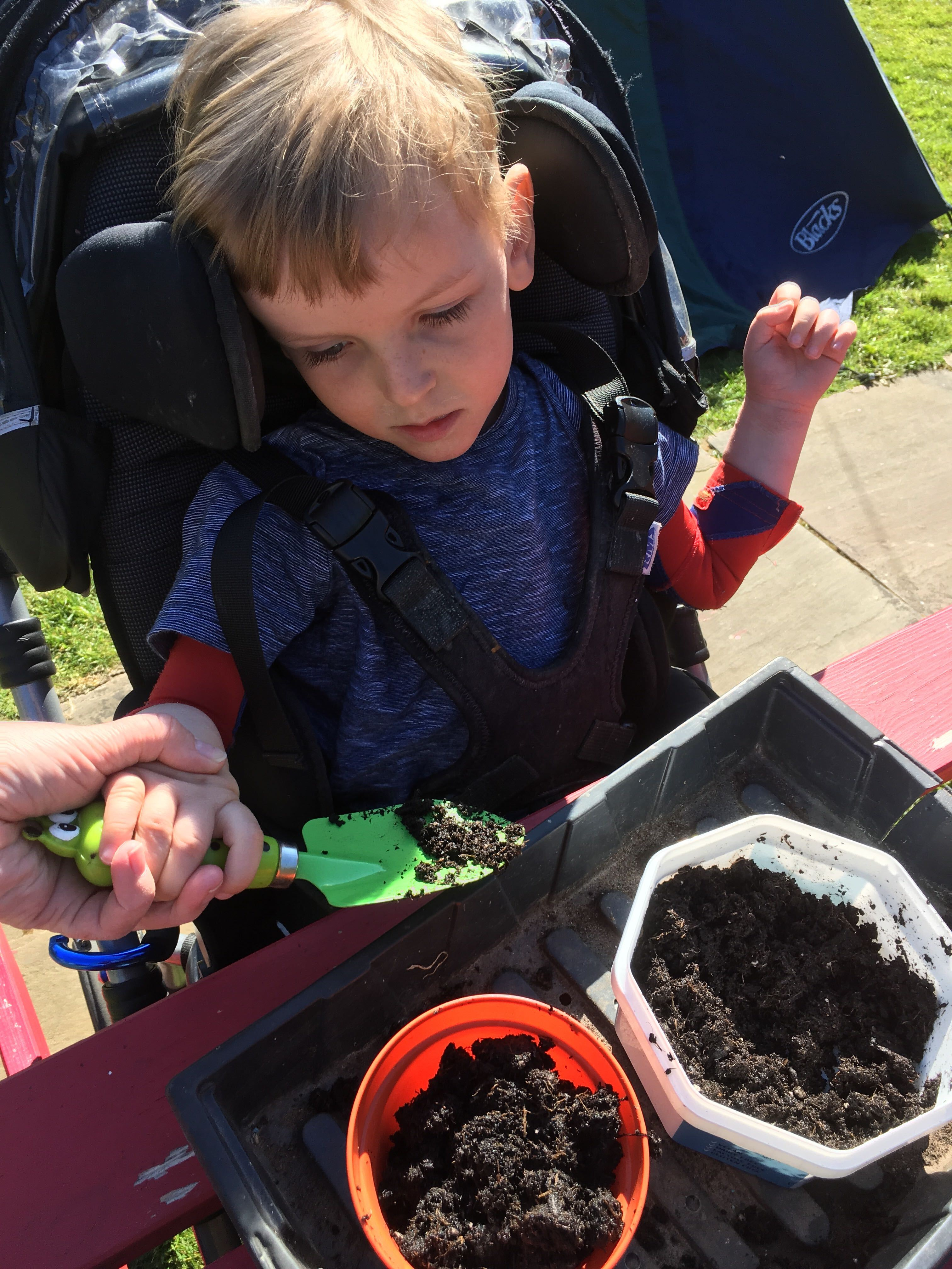 Photo of Quinns holding a green trowel moving soil from a plastic container into a plant pot guided by an adult hand