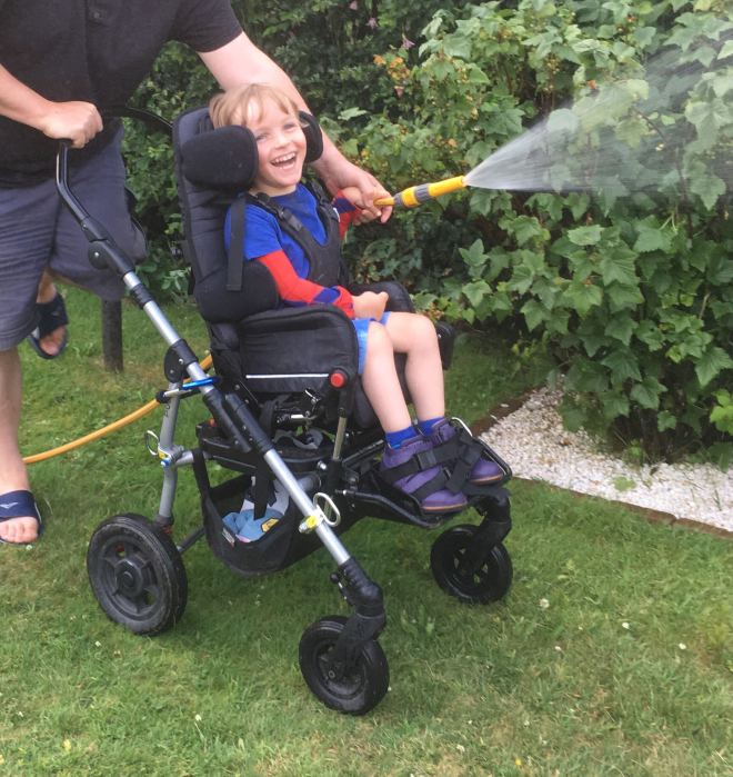 Photo of Quinns holding the hose to water fruit bushes supported from behind by Dad