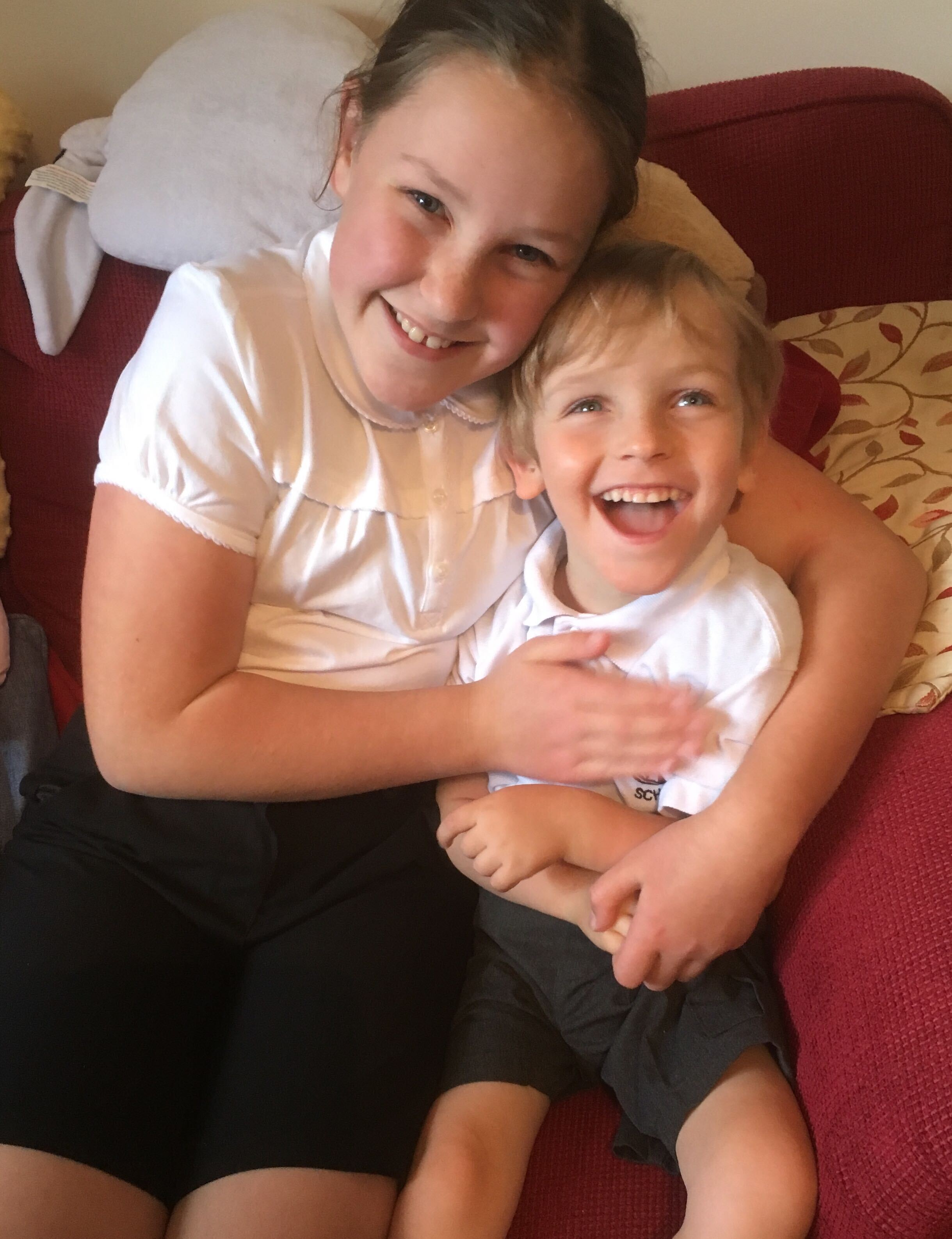 Photo of Big Sister and Quinns sitting together on a red sofa both wearing dark school shorts and white polo school polo shirts. They are both smiling.