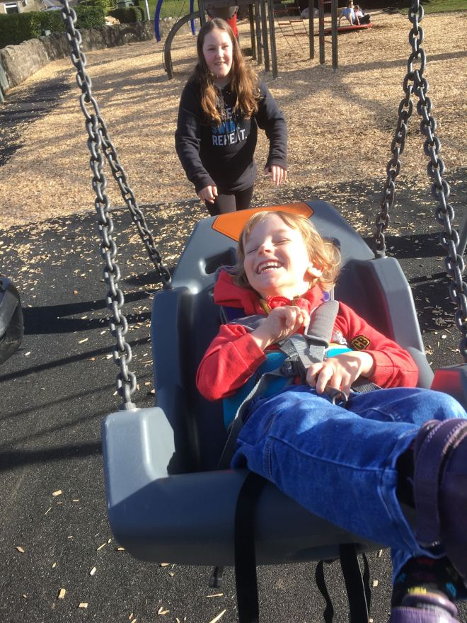 Five year old Quinns smiling while being pushed in a high backed swing by his ten year old big sister.