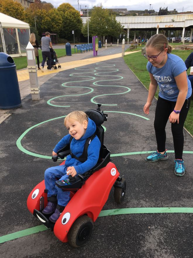 Four year old Quinns drives his 'Wizzybug' small electric wheelchair with his nine year old big sister chasing him from behind.